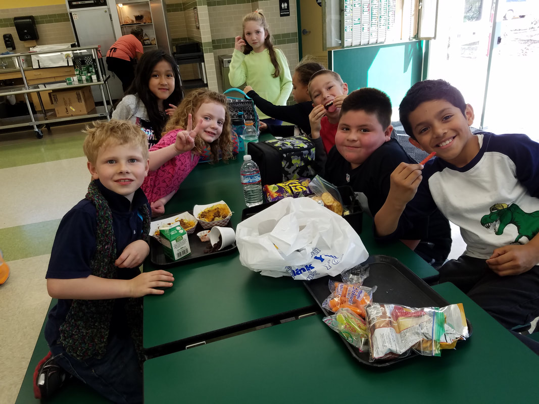 Picture of students at lunch time in the multi purpose room. Students have trays of food in front of them