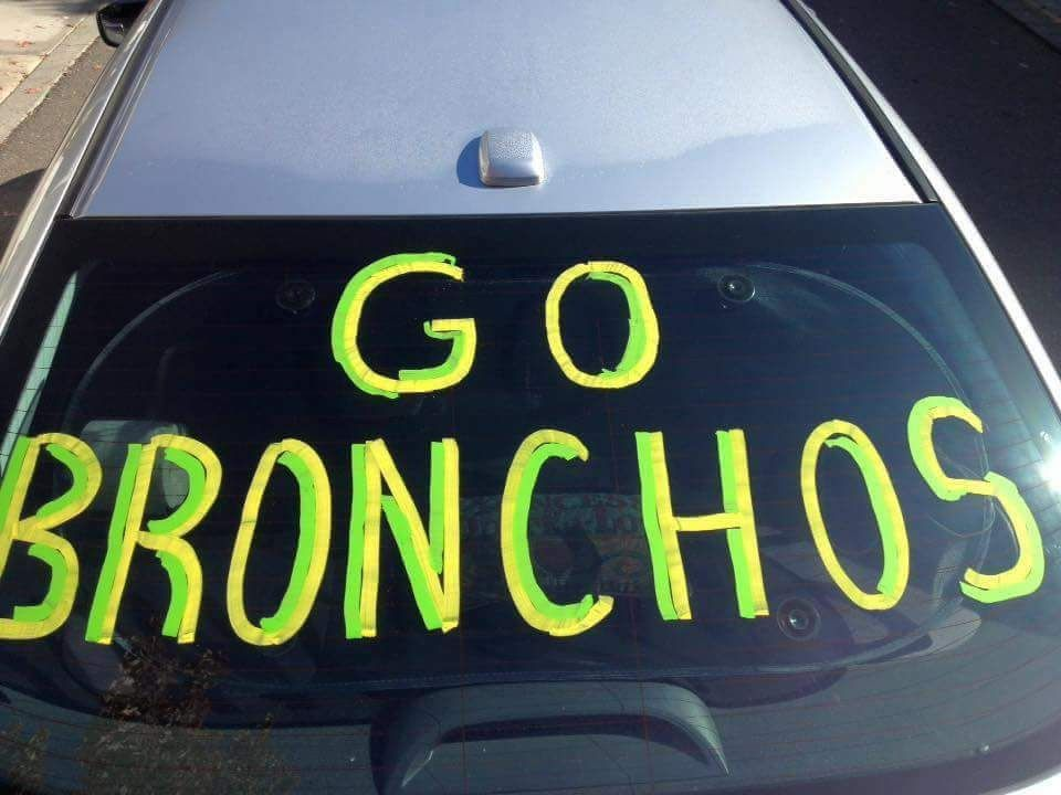 Photo of car windshield with GO BRONCHOS written on it in yellow & green